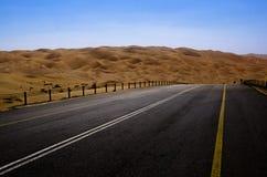 Straße, die durch Sanddünen in der Wüste von Liwa-Oase Vereinigte Arabische Emirate führt Stockfotos