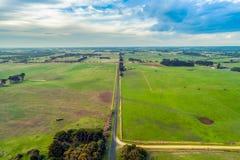 Straße, die durch Wiesen in ländlichem Australien überschreitet lizenzfreie stockfotografie