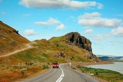 Straße, die zu Berge, isländische Landschaft führt Stockfoto