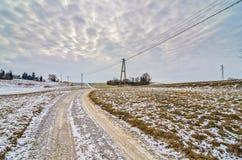 Straße, die zu Horizont durch ein Landschaftslandwirtschaftsfeld führt Stockfotografie