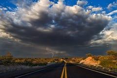 Straße, die zu stürmischen Himmel führt Stockbilder