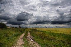 Straße durch das Feld in der Gewitterwolke Lizenzfreies Stockbild
