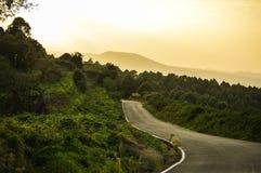 Straße durch die Berge durch Dämmerung Lizenzfreies Stockbild