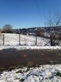 Straße durch die schneebedeckten Berge Stockbild