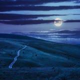 Straße durch eine Wiese auf dem Abhang nachts Lizenzfreies Stockfoto
