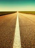 Straße durch Feld zum Horizont Stockbild