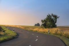 Straße durch Natur angesichts des Sonnenaufgangs Lizenzfreies Stockbild