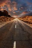 Straße durch Sonnenuntergangwüste Stockfotografie