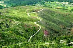 Straße in einer schönen grünen Gebirgslandschaft Stockbilder