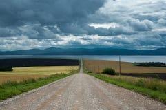 Straße entlang dem Feld zur Seeküste lizenzfreies stockbild