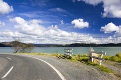 Straße entlang einem See mit weißen Wolken über ihm Stockbilder
