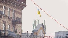 Straße geschossen vom Gebäude mit ukrainischem Flaggenfliegen auf Wind auf Himmel- und Stadthintergrund stock video