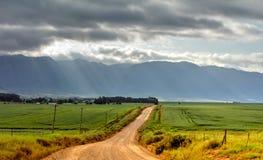 Straße, Grün-Felder, blaue Berge mit Sturm-Wolken Lizenzfreie Stockfotografie