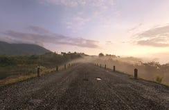 Straße im Morgen-Nebel und dem Sonnenlicht Stockfoto
