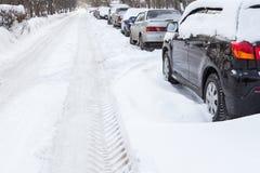 Straße im Schnee mit Autos auf dem Straßenrand Lizenzfreies Stockfoto