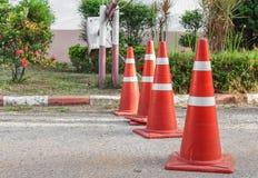 Straße mit dem Verkehrskegel Reihenverkehrskegelweiß und -orange Stockfotografie