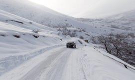 Straße mit einem Auto im Winter in den Bergen Lizenzfreie Stockbilder