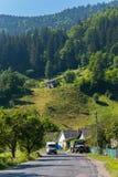 Straße mit einem Lastwagen und einem Kleinbus, die zu das Dorf auf der grünen Steigung des Berges, umfasst mit einem Koniferen fü stockfoto