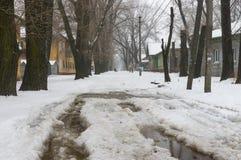 Straße mit großer Pfütze im Vorort der Dnepropetrovsk-Stadt am Tag des verschneiten Winters Lizenzfreie Stockfotografie