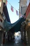 Straße mit Hängematte und Flaggen über der Straße zwischen Häusern Lizenzfreie Stockfotos