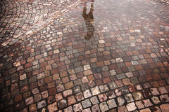 Straße mit Kopfsteinsteinen und Pfütze nach Regen Stockfotografie