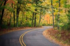 Straße mit Kurve durch Autumn Forest in Wisconsin Stockfotos