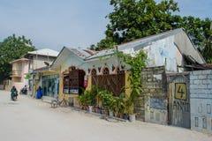 Straße mit lokalen Gebäuden, Fahrrädern und Leuten während des sonnigen Tages in der Tropeninsel Maamigili Lizenzfreie Stockfotos