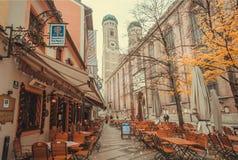Straße mit Tabellen von Bierkneipe und 15. Jahrhundert Frauenkirche-Kirche Stockbild