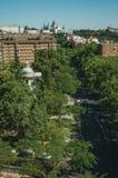 Straße mit Verkehr inmitten der Bäume und der Wohngebäude in Madrid stockbilder
