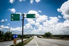 Straße mit Zeichenpfosten und blauem Himmel stockfotografie
