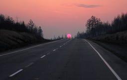 Straße nach Sibirien im Wintersonnenuntergang Lizenzfreies Stockfoto