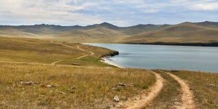 Straße nahe dem See mit Bergen im Hintergrund Stockfoto