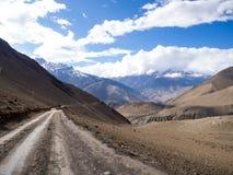 Straße in Richtung auf den Berg mit bewölktem Himmel in Abstand Stockfotos