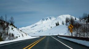 Straße in Richtung zu einem Schnee mit einer Kappe bedeckten Berg Stockbild