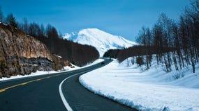 Straße in Richtung zu einem Schnee mit einer Kappe bedeckten Berg Stockbilder