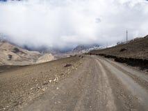 Straße in Richtung zum Berg im bewölkten Wetter, Lizenzfreies Stockbild