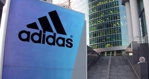 Straße Signagebrett mit Adidas-Aufschrift und -logo Moderner Büromittewolkenkratzer und Treppenhintergrund redaktionell Lizenzfreie Stockbilder
