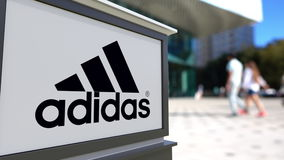 Straße Signagebrett mit Adidas-Aufschrift und -logo Unscharfe Büromitte und gehender Leutehintergrund Redaktionelles 3D Lizenzfreie Stockfotografie