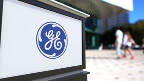Straße Signagebrett mit General Electric-Logo Unscharfe Büromitte und gehender Leutehintergrund Redaktionelles 3D Stockbilder