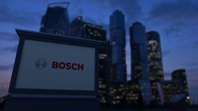 Straße Signagebrett mit Robert Bosch-GmbHlogo am Abend Unscharfer Geschäftsgebietwolkenkratzerhintergrund stock footage
