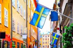 Straße in Stockholm mit schwedischen Flaggen stockfotografie