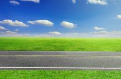 Straße und bewölktes Himmel- und Grünesgras Stockbilder