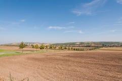 Straße und Feld auf Land, nahe kleinem Dorf im Hintergrund Stockfotos