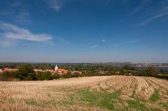 Straße und Feld auf Land, nahe kleinem Dorf im Hintergrund Lizenzfreie Stockfotos