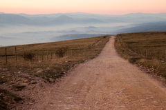 Straße und nebelhafte Berge Stockfotografie