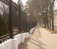 Straße und Zaun überschwemmt mit Sonne Stockbilder