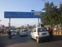 Straße voll des Verkehrs in Delhi mit obenliegendem Zeichen lizenzfreies stockbild