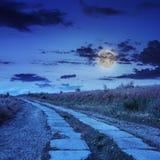 Straße von Betonplatten aufwärts zum nächtlichen Himmel Stockfoto
