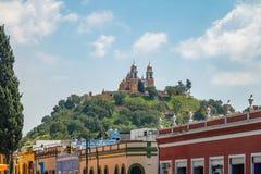 Straße von Cholula und Kirche unserer Dame der Abhilfen an der Spitze Cholula-Pyramide - Cholula, Puebla, Mexiko Lizenzfreies Stockbild