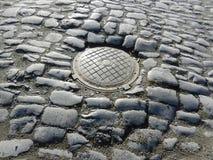 Straße von den Kopfsteinen mit Abwasserkanalluke Lizenzfreies Stockbild